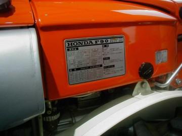 銘板部分。展示プレートにはホンダ初のディーゼル耕耘機、静かで低振動の2気筒・セル始動。ロータリーは着脱瞬時ワンチャック式でリモコン操作。 明るい2眼ヘッドライト採用。とあります。
