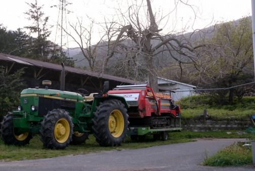 ジョンディアトラクター3050 堆肥を散布する機械をトレーラーに乗せています。季節は秋なのかなあ・・・春なのかなあ。手前のボサにヒメオドリコソウらしき影が見えるので春なのかもしれません。近くに山が見えます。背後のトタン屋根がいい感じ。