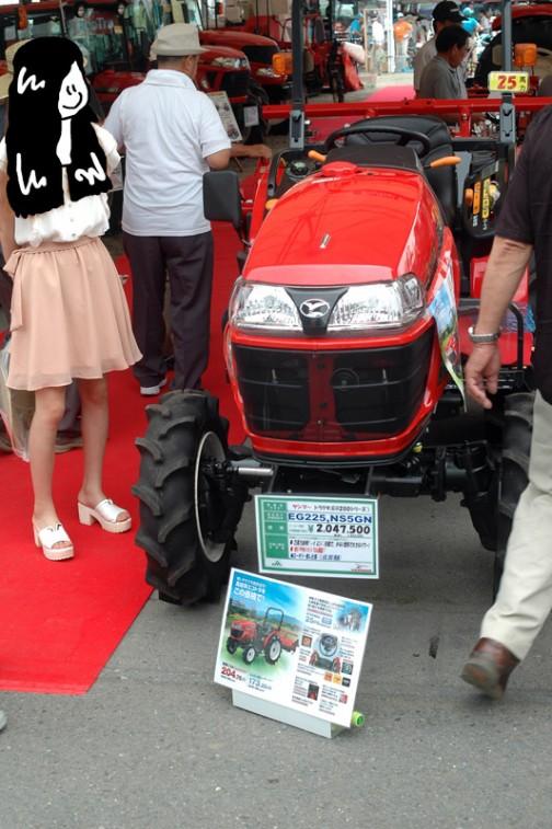 POPには、ヤンマートラクタ(EG200シリーズ) YANMAR TRACTOR EG225 NS5GN 価格¥2,047,500(税込み)  水冷4サイクル3気筒直噴ディーゼル 1330cc 25馬力(PS)  ●25馬力,直噴ディーゼルエンジン搭載で、少ない燃料で大きなパワー! ●使いやすいシンプル機能! ●ロータリー無し仕様:¥1,650,000(税抜)・・・とあります。傍らにはトラクターマニアの女の方、「トラ女?」がいらっしゃいます。