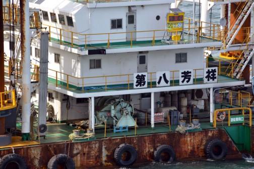 第八芳祥号とあります。調べてみると、姫路市の吉田組という会社のもので(遠い!!)最新鋭の施工管理システムを装備した25mグラブ式浚渫船(旋回式起重機船兼用)だそうです。大きさは57.0m×56.0mとほぼスクエア。主機関はヤンマーディーゼル6N280L-GN 2,500馬力×750回転/分 1基装備 第二次大戦時の戦闘機ぐらいのパワーでこのでっかい船を動かすことができるんですねえ・・・