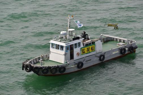 苫小牧港の監視船:進行方向と直角に舳先をこっちへ向けて小さな船が泊まっています。サイドには「監視船」一体何を監視しているのか・・・コイツが二隻います。