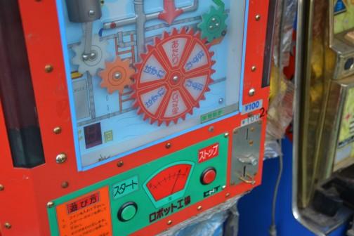 100円です!(その後100円で2回に変更されたようですが)1.コインを入れてください。2.スタートボタンを押してください。3.ギアが回り出します。4.ストップボタンを押してください。そのあとはよく見えませんが、5.あたりになると商品が下に出てきます。といった感じでしょうか?