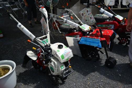 あれ?ここは関東農機株式会社のブースだったのかな? 左:関東農機株式会社の畑の入門管理機 さくらシリーズ K550-D 最大出力4.2馬力 前進2段後進1段 正逆転ロータリ 耕耘幅300mm 価格¥226,260 誰でも使えるカンタン操作。 ロータリ回転は高低2段でいろいろ使える。 Fモードは中耕・培土作業、Rモードは揚土作業。 Rモード時、車速は前進1段・後進1段に。 ハンドルを旋回して2通りの作業スタイル。 だそうです。  その右:読みにくいですが、同じく関東農機株式会社の鎮圧式整形管理機 うねパンチャー K802P   最大出力7.3馬力 前進4速後進2速 フルカットロータリ 溝幅280mm パンチャーボード 価格¥502,416 PTOからの動力で開閉するクッションボード採用、締まった畝作りはおまかせ下さい。 枕地が少ないからハウス内のスペースを有効活用。 鎮圧部は部品を減らして強度を保ったタフネス設計。 作業機前装タイプだから増し揚げ作業も楽々です。 だそうです。