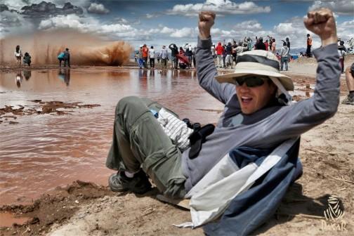泥しぶきを上げて走る競技車をたくさんの人が見に来ています。この人も大喜び。