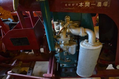 シバウラガーデントラクタ  1955年(昭和30) 石川島芝浦機械㈱ 製 (日本) AT-5型 9馬力 空冷エンジン搭載  1955年(昭和30) 本間は芝浦三輪トラクタを使用、のち国産四輪トラクタの発売でいち早く入れ替える。 80万円で購入。水田・酪農に有効に働いた。 25年使用後は、自家保存していた。  同型の全道での導入は92台。  SHIBAURA GARDEN TRACTOR  YEAR: 1955(Showa 30) Manufacturer: Ishikawajima Shibaura (Japan) Model: AT-5 Output: 9ps Engine: Air-cooled  In 1955(Showa 30)Mr.Honma was using a Shibaura three-wheelfe tractor.Upon the release of the 4-wheeled tractor he was one of the first to make the change over. He purchased this tractor for 8000,000 Yen. It perfonrmed well in all applications in the rice paddies and in the fields. After using this tractor fo 25 years, he continued to preserve its condition at his house.  Duaring production, 92 of this model were purchased in Hokkaido.