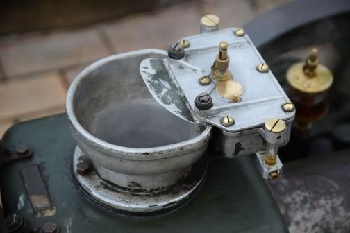 この発動機、いろいろ精密そうな真鍮の部品が付いていてすごく気になりました。これなんか何でしょう。オイルが入っているアルミケースみたいに見えますが、ホッパーのフチに引っ掛けるようになっています。湯気を受け取るようなフラップと滴下調整用なのか、真鍮のネジ。形、色、すごく高そうに見えます。もしかして、ノーマルの発動機をエンジンチューナーがチューニングしたエンジンとか、ワークスのエンジンとかだったりして・・・