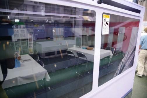 コンベヤで上まで上がって、見にくいですけど窓の中に見える緑の選別ベルトの上を転がっていきます。