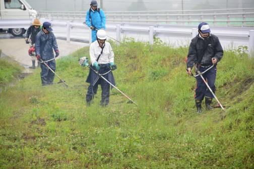 例によって集合場所の集落センターから二手に分かれて草を刈り始めます。通学路に沿って水路の法面などを刈ります。