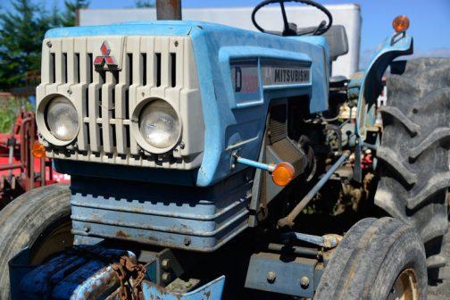 トラクターは正面部分にラジエターがあるので、だいたいヘッドライトの廻りがグリル状なものが多いです。他のメーカーが金属の網や、金属製のグリルにするところを、三菱は白いプラスチックで作ってしまっています。白いお面は三菱のとってもユニークな特長。