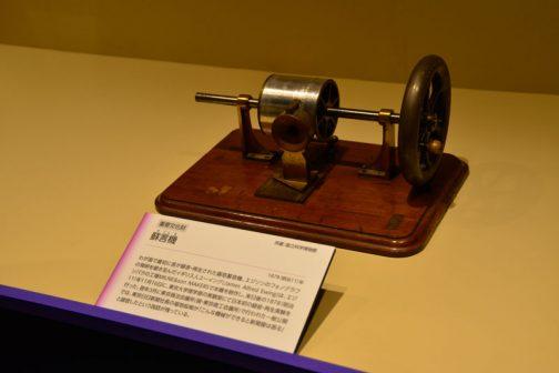 蘇言機(そごんき)1878(明治11)年 わが国で最初に音が録音・再生された錫箔蓄音機。エジソンのフォノグラフの発明を聞き及んだイギリス人ユーイング(James Alfred Ewing)は、エジンバラの工場MILNE&son MAKERSで本機を製作し、来日後の1878(明治11)年11月16日に、東京大学理学部の実験室にて日本初の録音・再生実験を行った。翌年3月に東京商法会議所(現・東京商工会議所)で行われた一般公開では、東京日日新聞社長の福地桜痴が「こんな機械ができると新聞屋は困る」と録音したという逸話が残っている。 とあります。機械の名前がおもしろいですね。蘇言機(そごんき)蘇ることばですものね!
