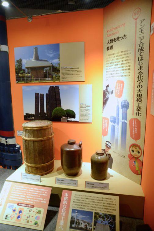 昔の台所にあったような容器が並んでいます。後ろ右のパネルには・・・ アンモニア合成ではじまる化学の大規模工業化 人類を救った技術 20世紀初頭にドイツで開発されたハーバー・ボッシュ法による空気中の窒素ガスを使ったアンモニア合成は、日本だけでなく、世界の本格的な近代化学工業の幕開けを告げる、しかも人類を救った画期的な発明でした。アンモニアから食料増産のための窒素肥料がつくられ、さらに、化学繊維や爆薬などの生産にも利用され、アンモニアを中心とした本格的近代化学工業が始まりました。 農業では緑肥などで空気中の窒素を固定して肥料に使っていましたが、それではまどろっこしい。直接取り出しちゃえ!ってことですね。 ある意味近代の技術は乱暴です。 「アンモニア合成は人類を救った技術なのよ」と、セルロイドのお人形さんがいっています。 もしかしたらこの人も空気中の窒素からで来ているのかもしれません。