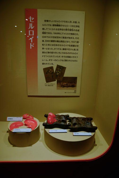 セルロイド  昔懐かしいセルロイドのお人形、お面。セルロイドは、植物繊維のセルロースを化学処理して作られる世界初の熱可塑性の合成樹脂である。1868年にアメリカで発明され、日本では20世紀初めに製造が始まる。その後、日本の重要な輸出商品となり、1937(昭和12)年には日本のセルロイド生産量は世界一となった。かつては、筆箱や石けん箱、玩具など身の回りのいろいろな物がセルロイドでつくられていたが、今では高級メガネフレーム、ギターのピックなど限られたものに使われている。 とあります。 セルロイドがモーレツに燃えやすいの、知ってます。小さい頃ピンポン球を拾ってきて、細かく砕いて金属のエンピツキャップに詰め、口を叩いて潰してロケットを作ってました。ライターであぶるとすごい勢いで飛んで行くんです。行き先はコントロールできません。今考えると火事にならなくてよかった・・・