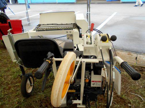 カタクラのネギ・ニラプランター 小さな機械ですが、必要人員は2人。椅子に座って1人が苗の供給を、そしてもう1人が歩きながら機械操作を担う感じです。