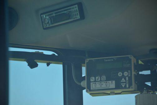 窓越しに中を撮っています。ちゃんとオーディオもあります。右下のパネルについては、タカキタのWEBページでは ネットの巻き数設定や、ベール成形数を記録する電子カウンターの表示、機械のエラーメッセージが表示できるコントロールボックスを標準装備し、運転席での操作、確認が容易にできます。 とされるコントロールパネルだと思われます。