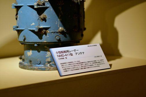 小型船舶用レーダー NMD-411型 アンテナ 波長3.2mm、尖頭出力30kw、最大探知距離80km、戦後GHQから気象レーダーの研究が許可されたのは1950(昭和25)年で、翌年に一般的なレーダーの研究が解禁となった。本装置はかつて日本館屋上で、実際に稼働させ展示していたものである。とあります。