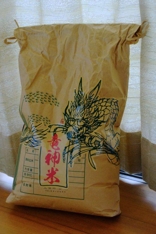原寸のシールを作って米袋に試し貼りです。かたちとしてはまあまあだけど、質感が違うよなあ・・・