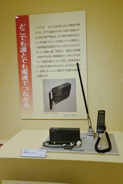 どこでも誰とでも電波でつながる かつてはどこにでも持ち歩ける電話が夢だった。1970(昭和45)年に大阪で開催された日本万国博覧会は、その夢の実現が近いことを印象づけた。15年後にやっと実現した携帯電話は肩掛けカバンほどの大きさであった。無線で電波を飛ばし、電話と交換機の技術があれば、携帯電話ができるわけではない。電波を細かく分けて使い、空間を飛び交う膨大な電波のなかから、それをキャッチし、混線しないように通信する高度な技術がひつようなのだ。 その下は自動車電話。そうそう!多くの人が見栄をはってインチキで付けていたのはこのアンテナです!