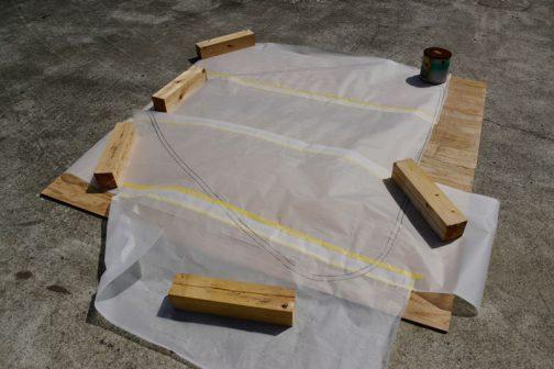 おにぎりの外枠、三角形を作ります。トレーシングペーパーに書いた形をベニヤ板に写しています。
