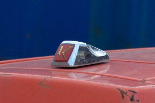 先端には「K」がはめ込まれたゴージャスなマスコット。後端に凹みが付いているところを見ると、ひねってフードをあける鍵になっているのかもしれません。
