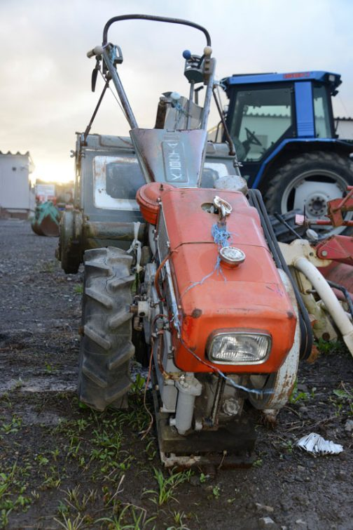 これがその耕うん機。トラクターの操作レバーは両手の手元の二カ所だけ。新しいものはハンドルの付け根部分にも操作レバーが並んでいるものが多いので、そこそこ古いものだと思います。メーカーはクボタ。写真が少なく特定に苦労しています。