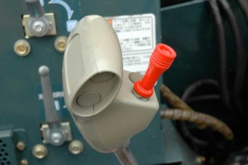 飛行機の操縦桿のようなレバーです。レバーにさらにスイッチが付いています。両手両足どころか、指まで使わなければなりません。