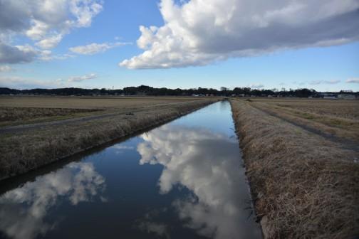 シーン・・・とした地上に比べ、空は少しドラマチック。鏡のような用水路に雲が映って、地面が割れちゃったみたいに見えます。