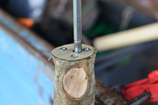穴の中にナットをエポキシとともにぶっ込み、上から接着剤を付けたトタンで押さえます。念のために木ネジを3本ほど・・・