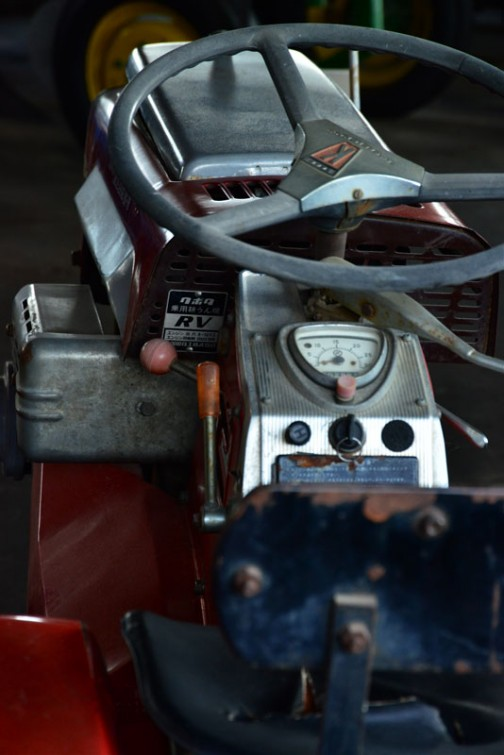 銀色のパネルが続く乗用トラクタの中心部分。説明板には、機種名:クボタトラクタ 形式・仕様:RY-70型 10馬力 製造国・国:(株)クボタ 日本 導入年度:1964(昭和39)年 使用経過:水田地帯に多く導入された機種で、乗用耕耘機として人気が高かった。 主な作業はロータリでの耕耘。とありますが、左奥の部分に・・・