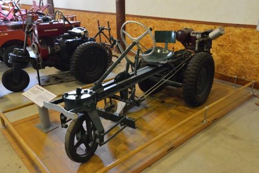 シバウラガーデントラクタ 1954年(昭和29) 石川島芝浦機械㈱ 製 (日本) AT-3型 6馬力 三輪タイプの空冷エンジン搭載 1954年(昭和29) 国産トラクタ初期のもの 国産三輪トラクタの開発が進み第一号機の実用に入り、2年前から各地で導入が盛んになる。 玉置は中古で入手活用したが前歴は不明。  同型の全道での導入は53台。  SHIBAURA GARDEN TRACTOR YEAR: 1954(Showa29) Manufacturer Ishikawajima Shibaura Model: AT-3 Output: 6ps Three-Wheeled tractor with air cooled engine  In 1954(Showa29) this was the first domestic built tractor in japan. With the advances in the development of domestic three wheeled tractors, this model was in great demand-up 2 years prior to the actual unveiling of Mr. Tamaki purchased this tractor second hand and use it for some period of time. The history of this particular machine is uncertain prior to Mr. Tamaki purchasing it.  Duaring production, 53 of this model were purchased in Hokkaido.