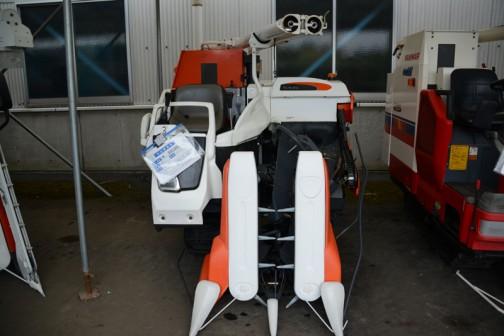 クボタコンバインAR218Gです。AR218Gの安全鑑定は2002年。乗用型 2条 刃幅 75cm 機関 D1105-C-11型水冷4サイクル3気筒ディーゼル1123cc、18.0馬力/2500rpm グレンタンク式。当時の希望小売価は¥2,750,000〜¥3,000,000。値札には、クボタコンバイン AR218G 価格¥800,000 使用時間319時間 購入初年度H15年(2003年)HSTベット、テンションプーリー交換、成約後修理対応。と書いてあります。