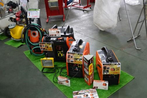 いちばん奥の黄色いタンク噴霧器かなあ¥99,800 その手前オレンジの高圧洗浄機 JC-8060E(50hz)JC-8060W(60hz)価格¥29,800 どうも京都府長岡京市の株式会社工進という会社の製品のようです。 インバーター発電機 GV-28i  定格出力2.8kVA 連続運転時間4.1〜9.4時間 価格¥128,000 インバーター発電機 GV-16i  定格出力1.6kVA 連続運転時間4.7〜11.5時間 価格¥89,800 インバーター発電機 GV-9i  定格出力0.9kVA 連続運転時間3.7〜5.8時間 価格¥59,800 パソコンも使える高品質電源だそうです。