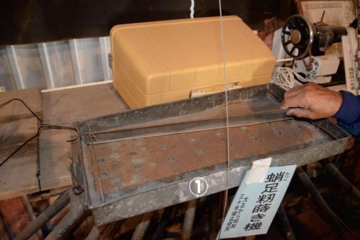 ①たこ足籾蒔き機 皿の上に籾を置いておき、この板を動かすことによって穴から籾が田んぼに落ちるようになっているようです。