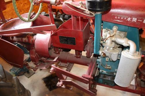 こちらはシバウラガーデントラクタ  1955年(昭和30) 石川島芝浦機械㈱製。やはり長いレバーが手元に来ています。自転車のブレーキみたいなのを握ってロックを解除し、引っぱるようになってるんですね。