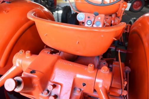 そのシートの形状とは全く別で、美しいトラクター本体。作業機で巻き上げるホコリよけのカバーでも付けたのか、ホックが点々と付いています。