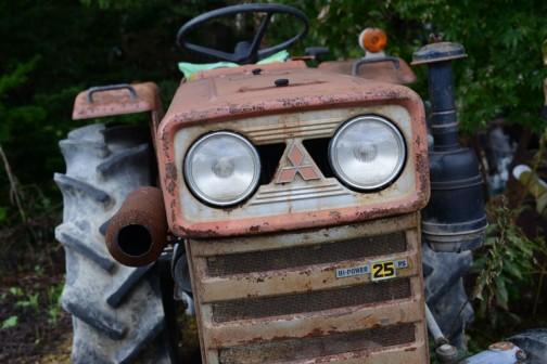 三菱トラクターR2500Gです。tractordata.comによれば、青いDトラの前の赤い三菱・・・1970年〜1975年製造。車体のプレートによると、1192cc2気筒ディーゼル25馬力/2700rpmです。