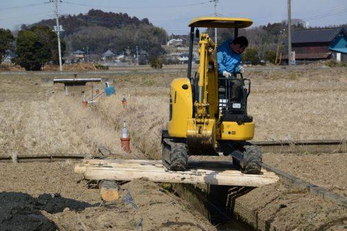 畦を潰さないように、そして水路をまたぐため、材木をレール状に敷いて作業をしています。