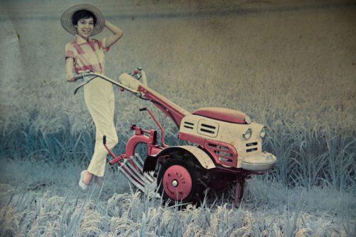 ポーズをとる女性は農機お約束のチェック(かなり大きいですが)のシャツ。しかし、とても農作業はできそうもないパンプスを履いています。 ・・・・ そんなことより、このフルカバードの耕耘機、まるっこいデザイン、ホイールキャップはデイッシュ型でめちゃめちゃ格好いいじゃないですか!!!