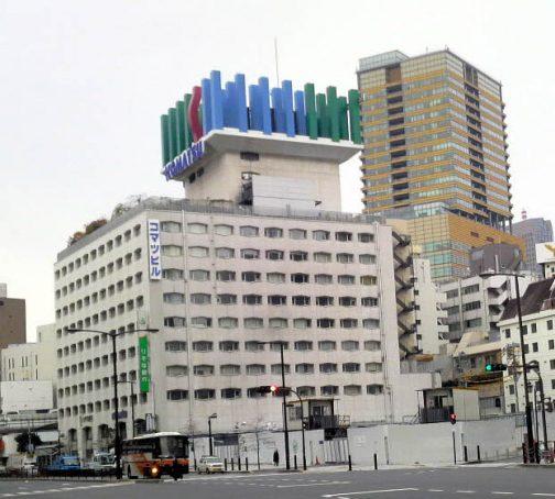 """ただ、塔屋の上には何か乗せるようにできていたらしく、Wikipediaにこのような写真が載っていました。 コマツのWEBページによれば、これは屋上モニュメントというもので、題してSPACE 「いのちの森」というそうです。 2001年5月、創立80周年を記念して、東京港区の本社ビル屋上に、環境との調和をテーマとした空間"""" SPACE 「いのちの森」"""" を設置しました。"""" SPACE 「いのちの森」"""" は、屋上モニュメントと、3つの庭園で構成されています。 とありました。 詳しくはコマツのWEBページでとうぞ!ただし、巨大ブルドーザーのことは載っていませんでした。"""