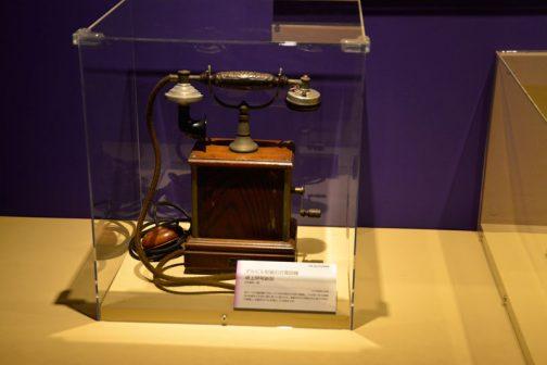 デルビル型磁石式電話機 卓上甲号新型 日本電気製 1929(昭和4)年頃 ガワーベル電話機に代わって1896(明治29)年に登場し、その後1963(昭和38)年頃までの長い間に渡って使われた。電話をかけるときは外の取手を回して発電し、交換手のベルを鳴らして合図する。交換手は口頭で電話番号を聞くと、手動で先方に繋ぐ。 とあります。ガワーベル電話機とはでかいイヤホンのようなものをてで耳に押し当て、電話機に備え付けられた送話口に向かって話す、国産第一号機のようなタイプの電話機で、このように送話器と受話器がハンドセットになっている現在の電話機のようなものではありませんでした。よく考えたらこのデルビル型、ダイヤルはないですけど今の電話と基本的に変わっていないですものね。