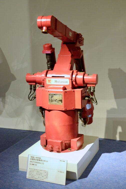 初期の頃の安川電機の産業用ロボット この展覧会のカタログの産業用ロボットのキャプションには 現代のモノづくりの場において、産業用ロボットの果たしている役割には、大きなものがあります。そのはじまりは1950年代。アメリカで概念が提唱され、ユニメート社によって、初めて実用化されました。日本においては川崎航空機工業が輸入・国産化し、国内でも産業用ロボットの開発が進みました。  1970年代になると、産業用ロボットの研究も盛んになり、各社からいろいろなロボットが開発されるようになります。安川電機が1977(昭和52)年に国内で初めて開発・販売された全電気式の産業用ロボットは、従来の油圧式から全電気式にしたことで、位置や速度の制御製に優れ、かつ、保守点検が容易なことから、従来熟練を必要としたアーク溶接の自動化を担い、わが国の自動車産業の品質の安定化とコストダウンに貢献しました。こうしたロボットが日本の工業を発展させたのです。 とありました。