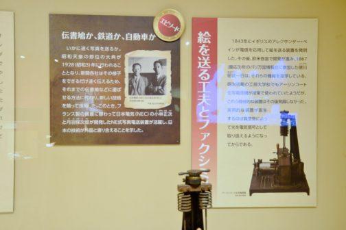 左;エピソード 伝書鳩か、鉃道か、自動車か  いかに速く者sんを送るか。昭和天皇の即位の大典が1928(昭和3)年に行なわれることとなり、新聞各社はその様子をできるだけ速く伝えるため、それまでの伝書鳩などに運ばせる方法に代わり、新しい技術を競って採用した。このときフランス製の装置に替わって日本電気(NEC)の小林正次と丹羽保次郎が開発したNE式写真電送装置が活躍し、日本の技術が外国と渡り合えることを示した。 右のパネル 絵を送る工夫とファクシミリ 1843年にイギリスのアレクサンダー・ベインが電信を応用して絵を送る装置を発明した。その後欧米各国で開発が進み、1867(慶応3)年のパリ万国博覧会に参加した徳川昭武一行は、それらの機械を見学している。明治初期の工部大学校でもアーリンコート生写真電信機が授業で使われていたようだが、これら機械的な装置はその後発展しなかった。実用的な装置が誕生するのは真空管によって光を電気信号として取扱えるようになってからである。