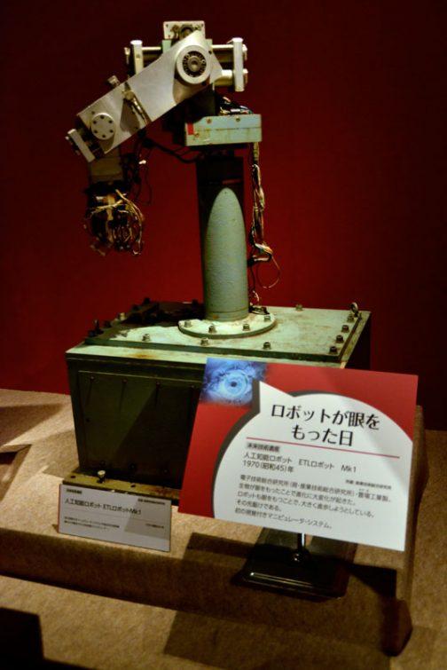 最後の始まりはロボットです。 ロボットが目を持った日 人工知能ロボット ETLロボット Mk1 1970(昭和45)年 電子技術総合研究所(現・産業技術総合研究所)・萱場工場製。生物が眼を持ったことで進化に大変化が起きた。 ロボットも眼を持つことで、大きく進歩しようとしている。 その先駆けである。 発の視覚付マニュピュレーターシステム。 とあります。見た目は角も取らない荒削りのロボットアームですが、これが先駆けなんですか・・・