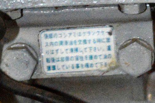 ステッカーには 後部のコシアミはクランクケース内の潤滑油を交換するときに取りはずして清掃して下さい。運転後は右側の盲栓を緩めて油の循環している事を確かめてください。 と書いてあります。 何の変哲もない注意書きです。