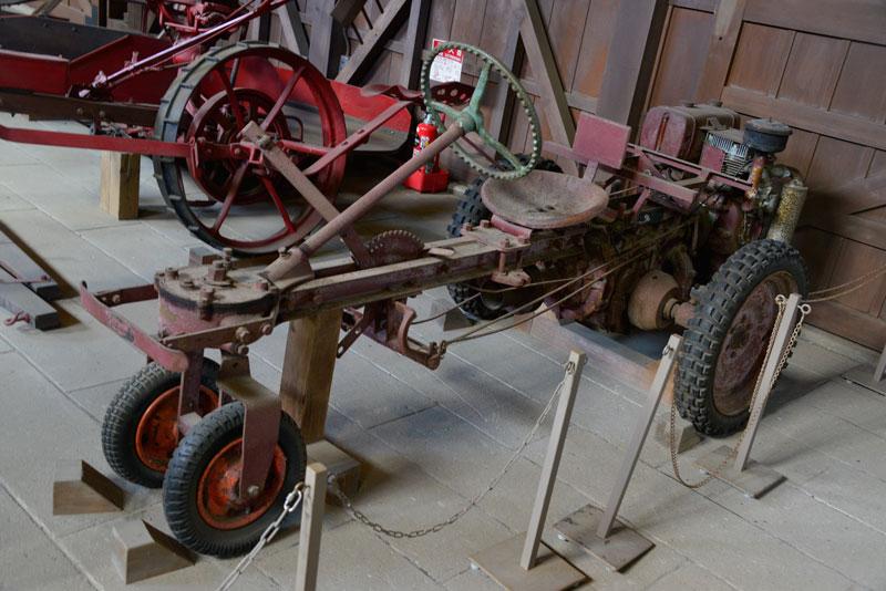 そしてこれが北海道開拓の村で見たシバウラガーデントラクターAT3。三輪のトラクターのはずですが、前輪に一輪車のタイヤが2つ。変則4輪の構成になっています。これはもちろん後から持ち主が改造したものなのでしょう。初期のトラクターは自分の作業スタイルに合わせて「カスタマイズ」するというのがお約束だった感じがします。サービス網も整備されていないでしょうし、部品の供給だって怪しかったでしょうし・・・ 後方に置かれたエンジンのコントロールをするために紐っぽいものを使っているのがおもしろいです。