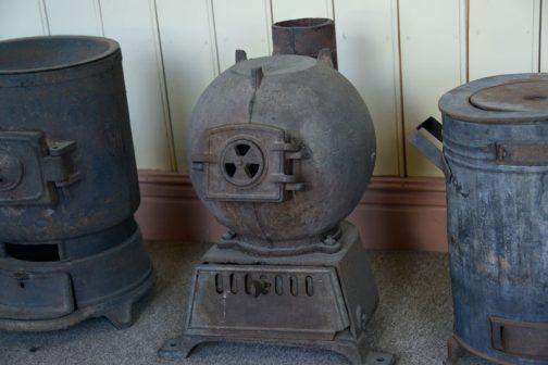 キャプションによるとこれは地球形ストーブ。以下引用します。 地球形ストーブ 石炭ストーブの一種で、列車の暖房具として用いられた。明治30年代から使用され、通称「タコストーブ」として多くの人に親しまれた。燃焼筒の丸い独特な形は乗客が魚や餅などを焼いて匂いや煙で車内が汚れるのを防ぐためともいわれる。