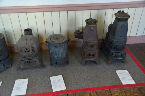 で僕が気になったのが右の2つのストーブ。キャプションを引用しますと 貯炭式ストーブ 貯炭槽に石炭を詰め、長時間燃え続ける貯炭式ストーブは、炭を入れる際に出る煤煙が部屋に充満することもなく、お座敷でも使えるストーブとして人気が高かった。昭和初期には国産の安価な貯炭式ストーブが普及し、長い間家庭用石炭ストーブとして利用された。とあります。