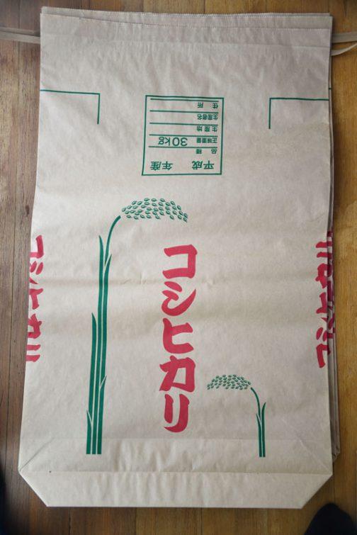 近所のMさんのところで本物の米袋を数枚もらってきました。以前の調査でこの米袋は3重になっていることがわかっていますから、こいつをバラせば共布(この場合は共紙)が手に入ります。そいつに印刷して上から貼り付けてしまえばオリジナルの米袋ができると考えました。